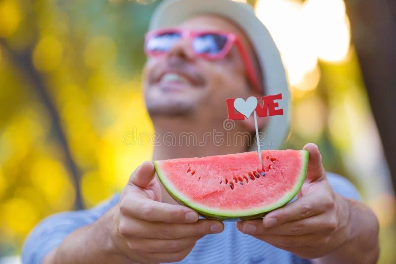 Stående av mannen som ser på himmel- och innehavskiva av vattenmelon royaltyfria bilder