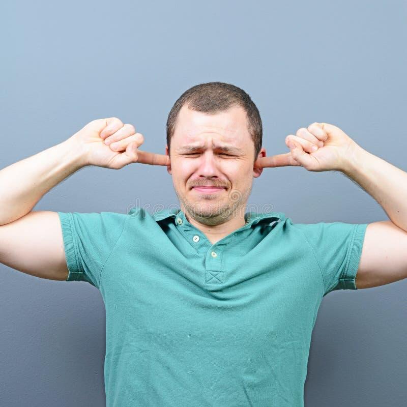 Stående av mannen som täcker öron med händer mot grå bakgrund arkivfoto