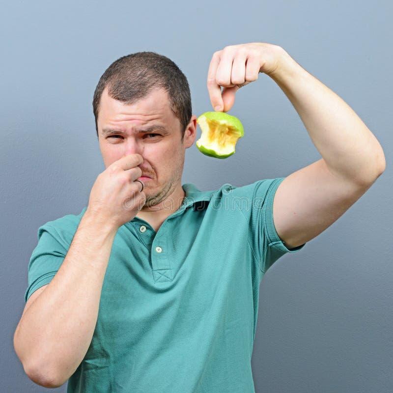 Stående av mannen som täcker näsan med handen som visar det ruttna äpplet mot grå bakgrund fotografering för bildbyråer