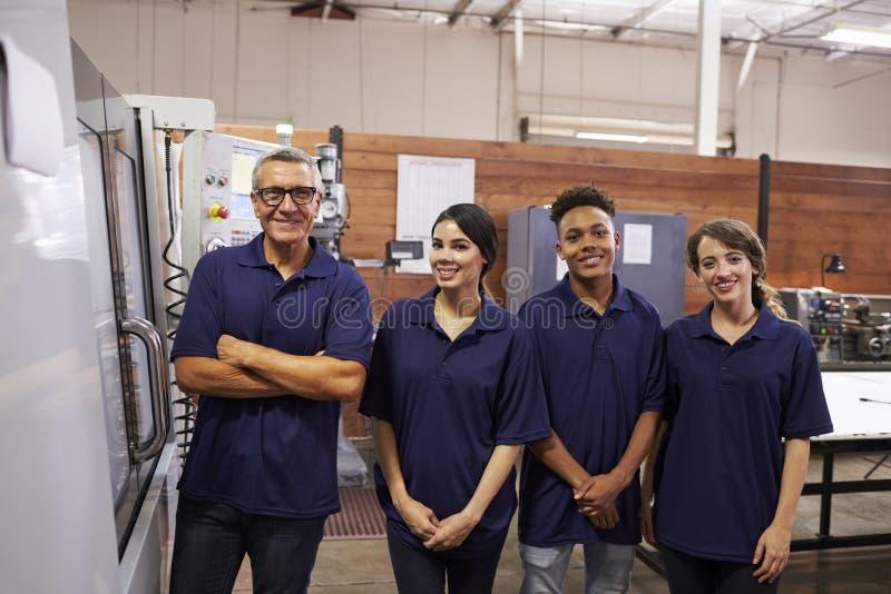 Stående av maskinen för teknikerTraining Apprentices On CNC royaltyfria foton