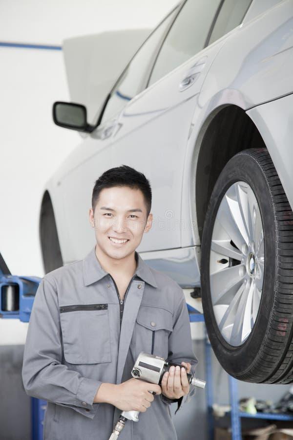Stående av mekanikern med makthjälpmedlet bredvid bilhjulet som ser kameran royaltyfri foto