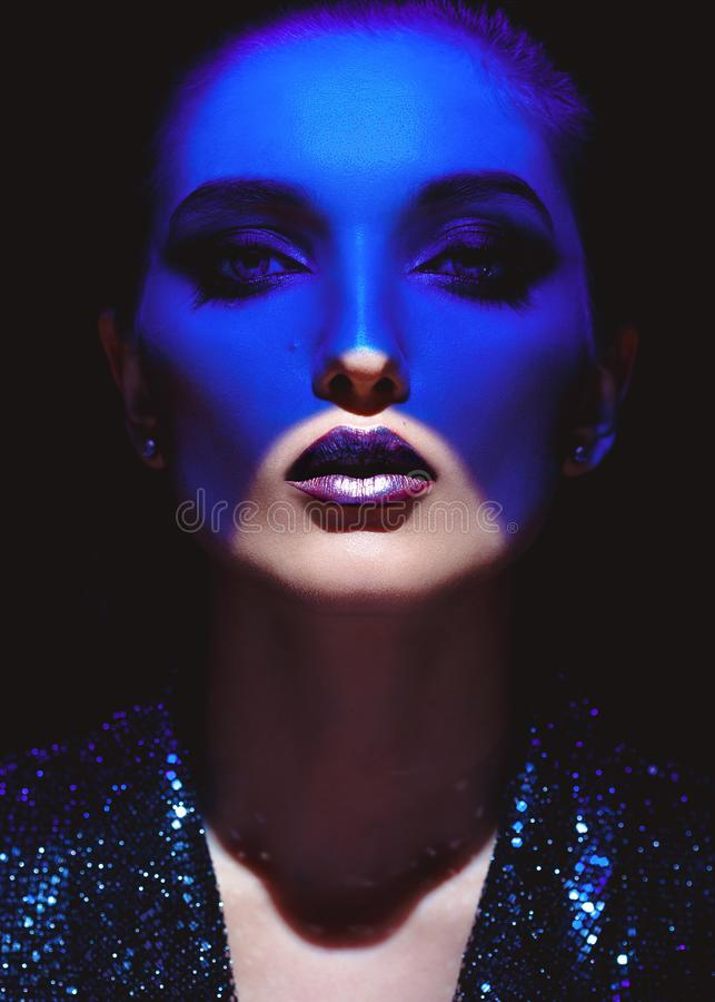 Stående av modeflickan med stilfull makeup och blått neonljus på hennes framsida på den svarta bakgrunden i studion royaltyfri foto