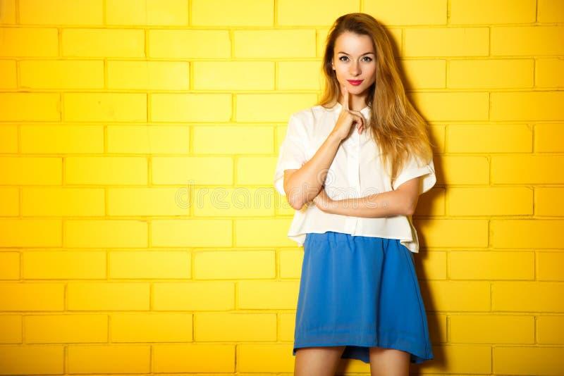 Stående av modeHipsterflickan på den gula väggen arkivfoton
