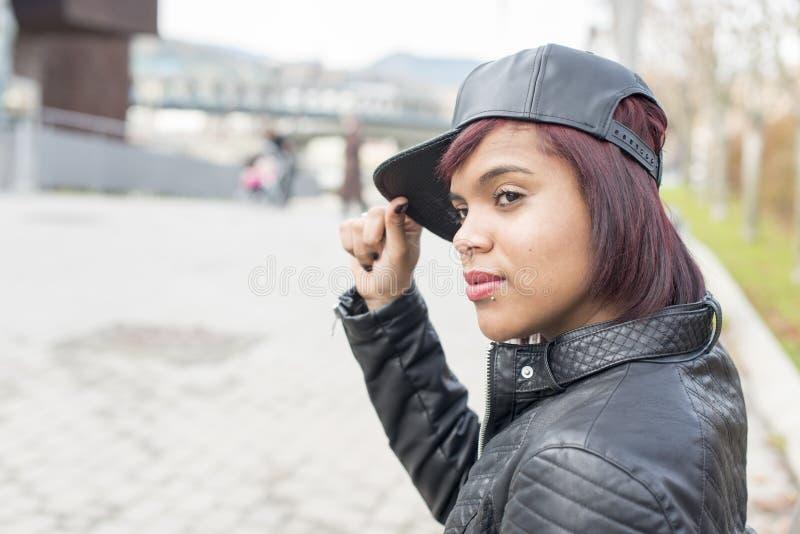 Stående av modekvinnan med baseballmössan som bort ser, urba royaltyfri fotografi