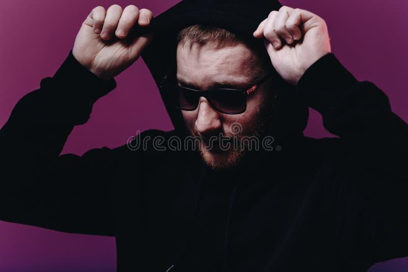 Stående av modemannen i en svart tröja med en huv och solglasögon i neonljus i studion royaltyfri fotografi