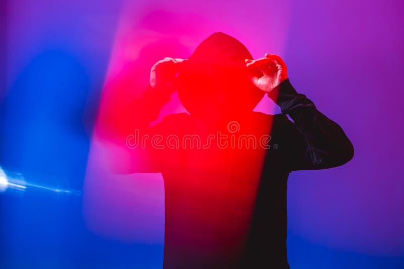 Stående av modemannen i en svart tröja med en huv och solglasögon i neonljus i studion arkivbild