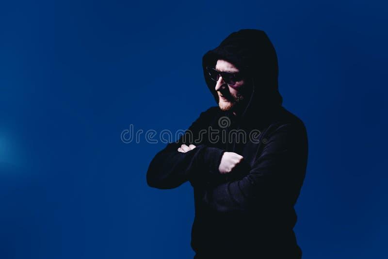 Stående av modemannen i en svart tröja med en huv och solglasögon i neonljus i studion royaltyfri bild