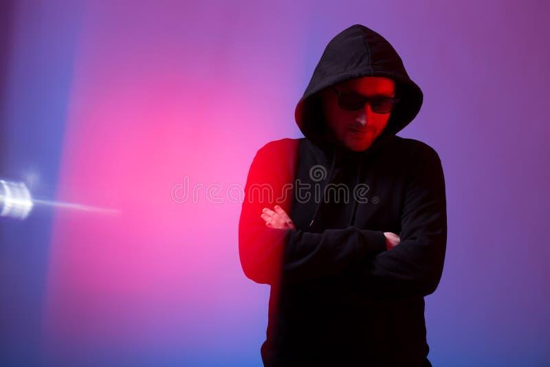 Stående av modemannen i en svart tröja med en huv och solglasögon i neonljus i studion royaltyfria bilder