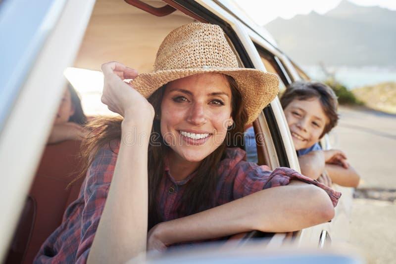 Stående av modern och barn som kopplar av i bil under vägtur royaltyfria foton