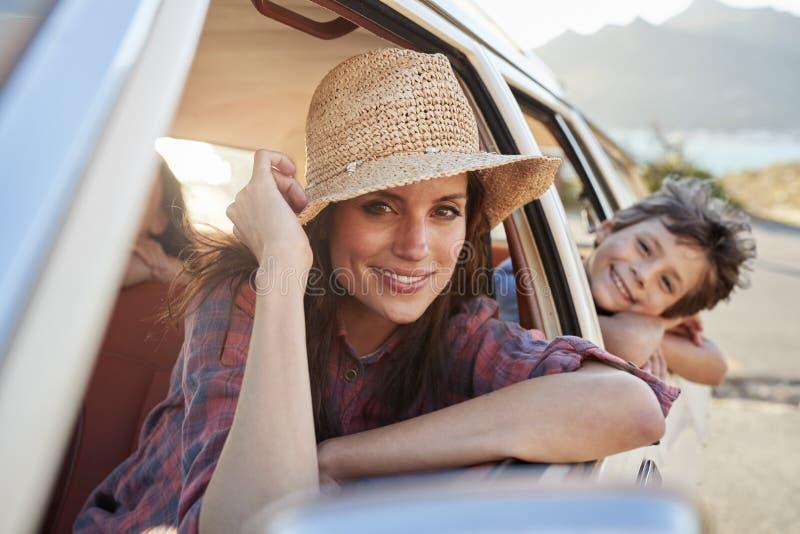 Stående av modern och barn som kopplar av i bil under vägtur arkivfoto