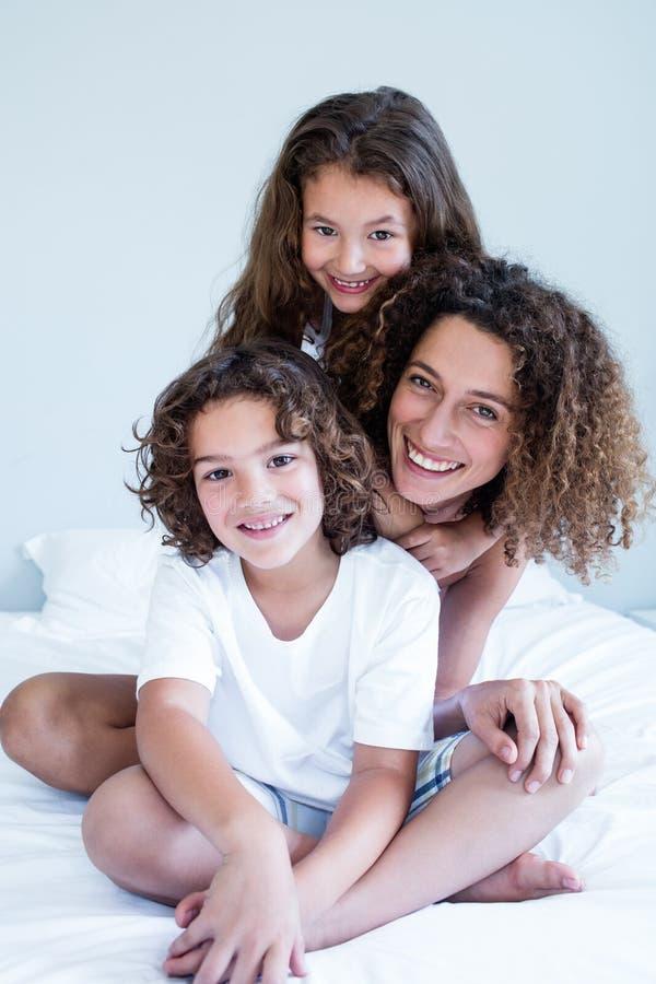 Stående av modern och barn som tillsammans sitter på säng arkivfoto