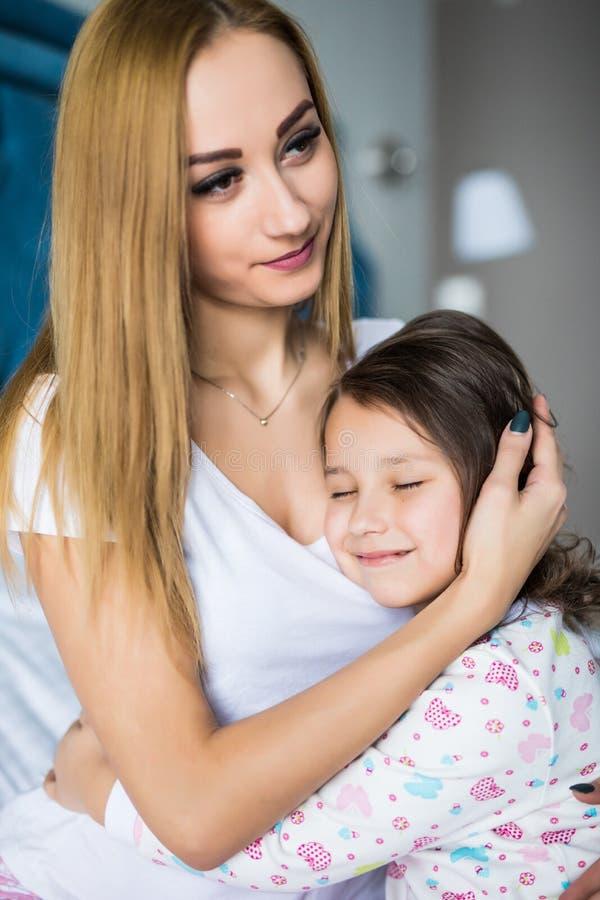 Stående av modern och dottern som lägger i säng som hemma kramar och ler fotografering för bildbyråer