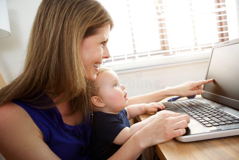 Stående av modern och sonen som hemma använder bärbara datorn arkivbild