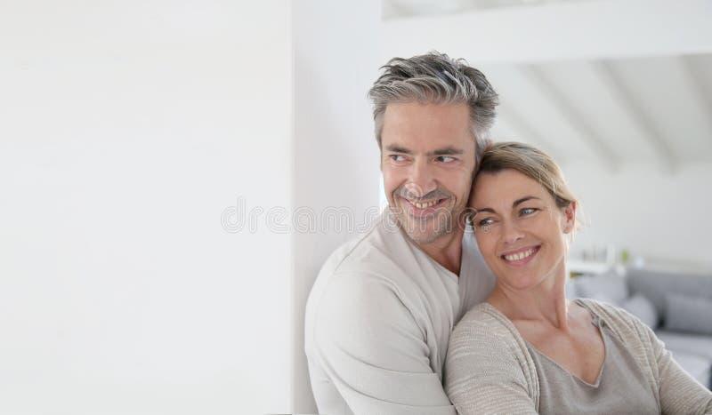 Stående av mogna par som hemma omfamnar arkivbild