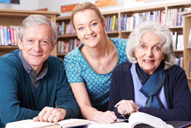 Stående av mogna studenter som arbetar med läraren In Library arkivfoto