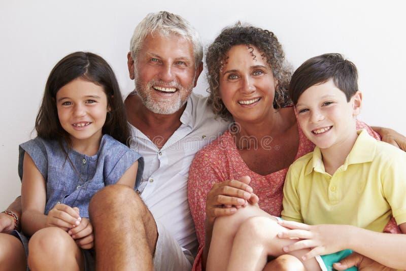 Stående av morföräldrar med barnbarn som sitter vid väggen arkivfoto