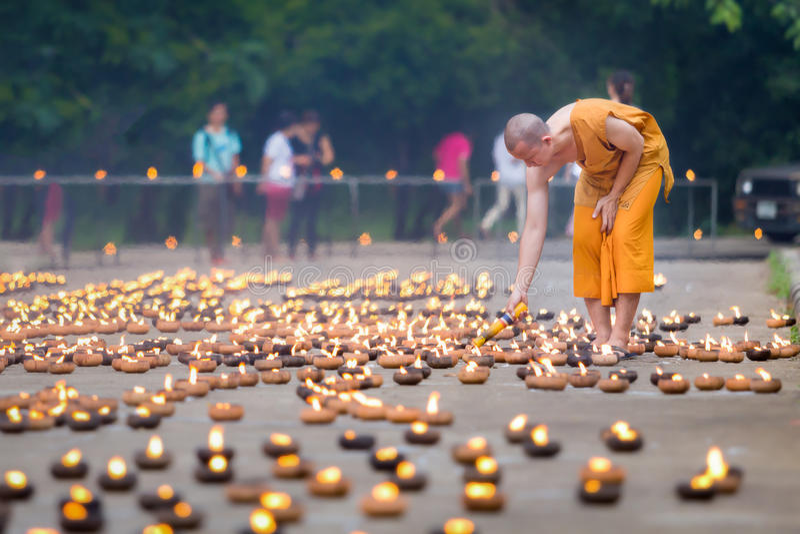 Stående av munkar som upp tänder levande ljus inom en buddistisk vikarie royaltyfri foto
