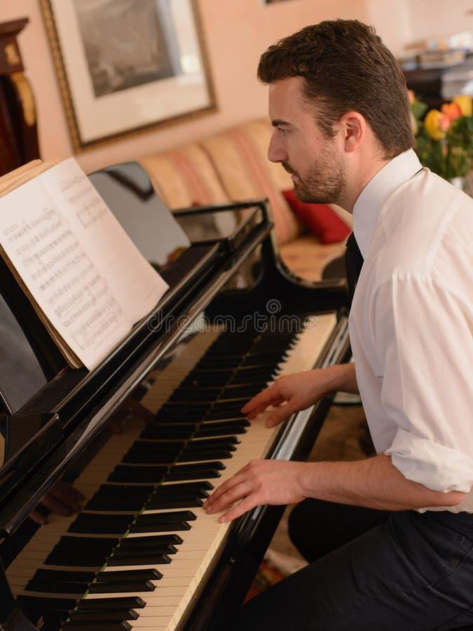 Stående av musikaktören som spelar hans piano royaltyfri bild