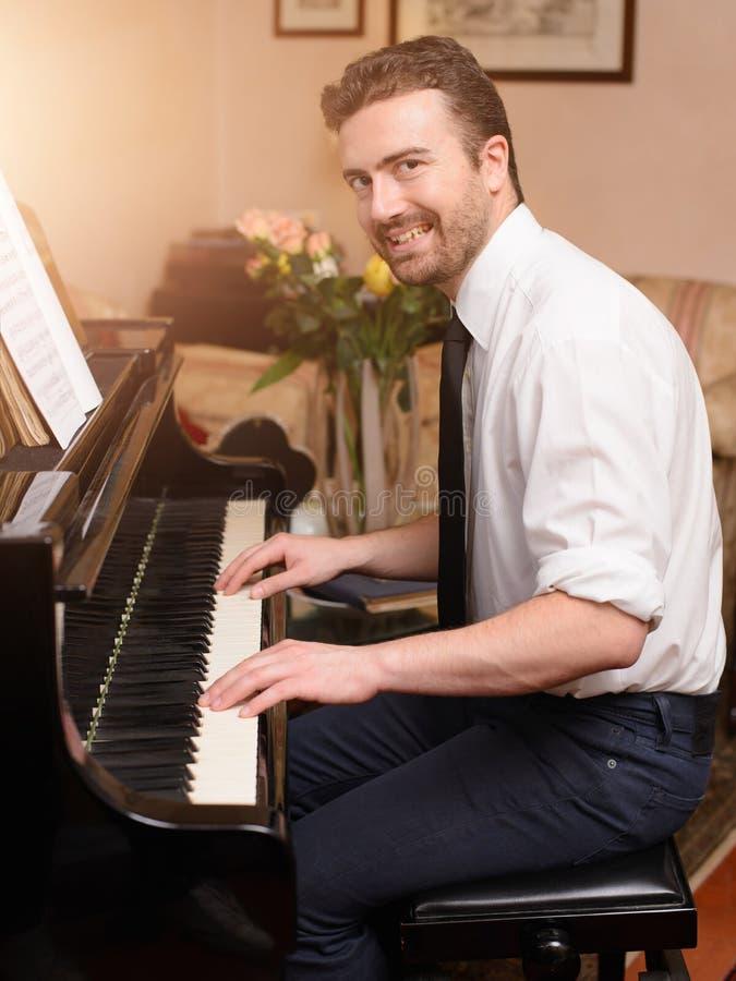 Stående av musikaktören som spelar hans piano arkivbild