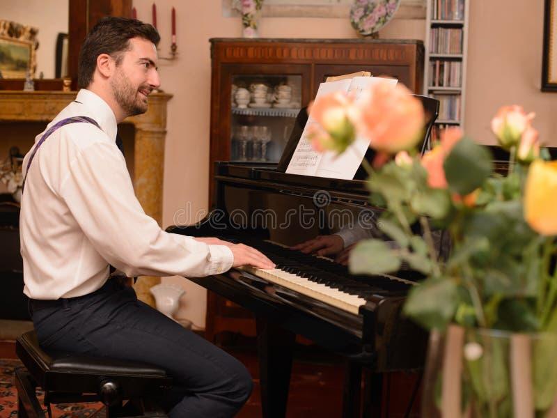 Stående av musikaktören som spelar hans piano arkivfoto