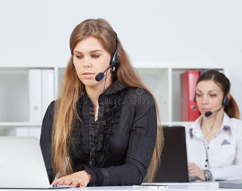 Stående av nätt kvinnlig helpdeskanställd med hörlurar med mikrofon på arbetsplatsen arkivbild