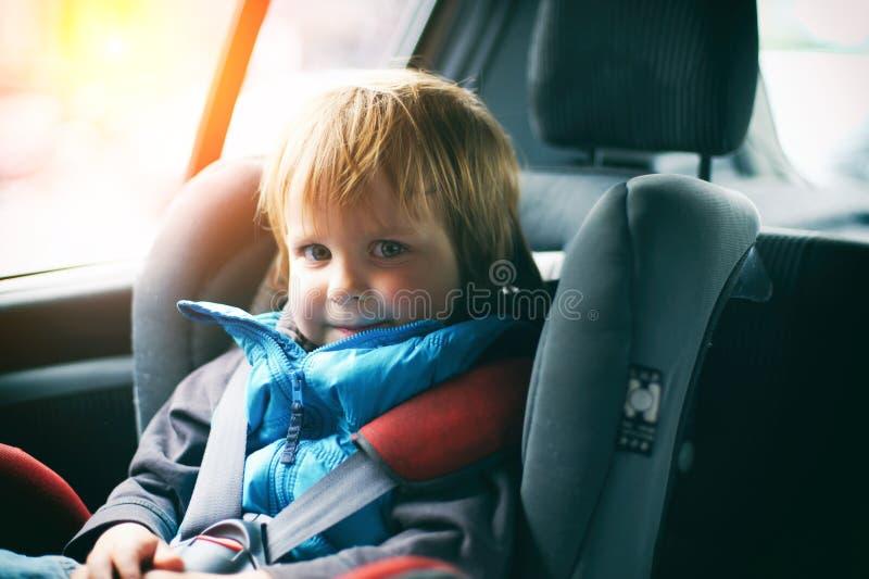Stående av nätt litet barnpojkesammanträde i bilsäte Barntrans.säkerhet arkivfoton