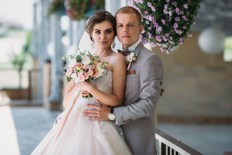 Stående av nygifta personer på bröllopdag Brudgummen i en grå dräkt med en vit skjorta och en fluga kramar en härlig brud royaltyfri fotografi