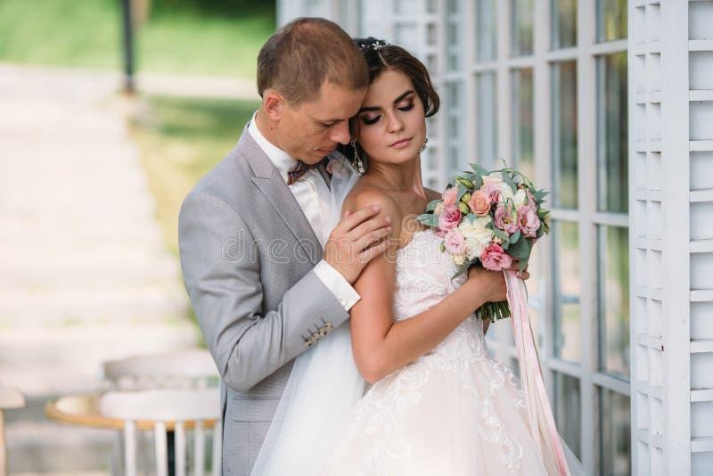 Stående av nygifta personer på bröllopdag Brudgummen i en grå dräkt med en vit skjorta och en fluga kramar en härlig brud royaltyfri bild