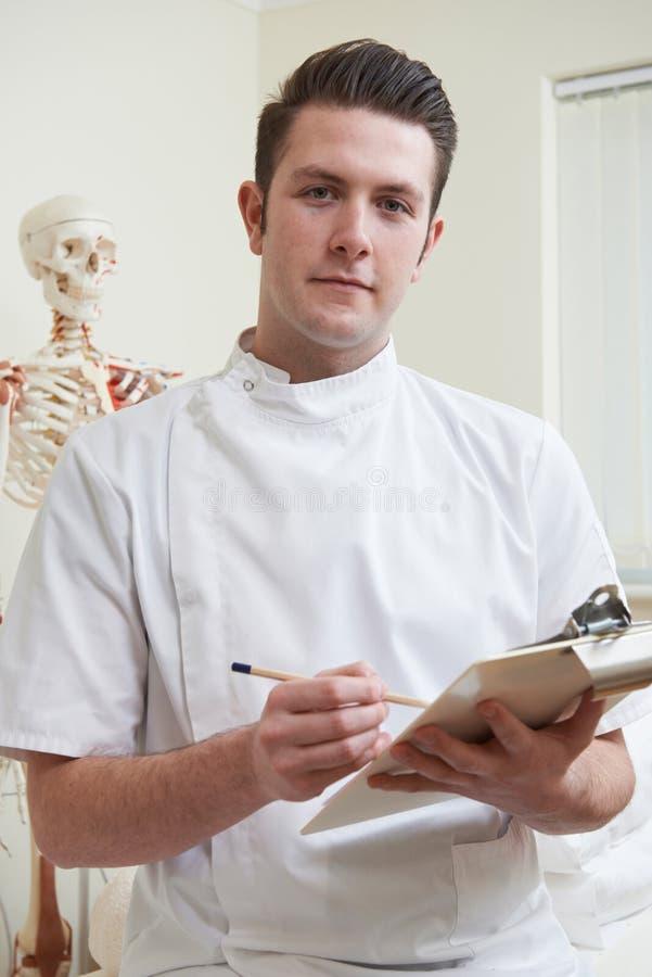 Stående av osteopaten i konsulterande rum royaltyfri bild
