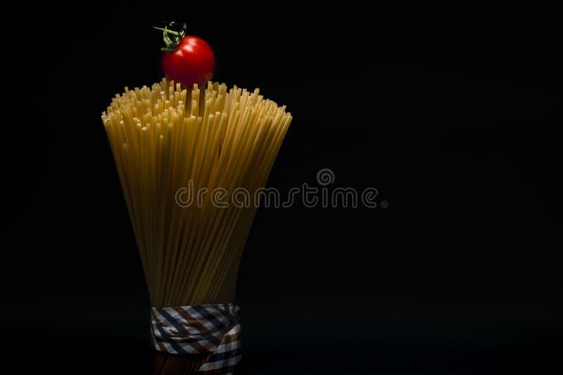Stående av packad modespagetti som överst binds med bandet på mörk bakgrund med tomaten arkivbild