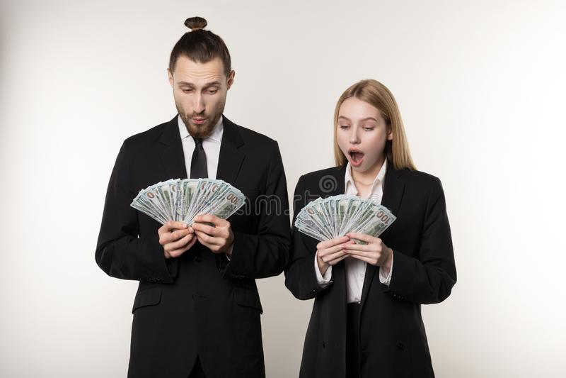 Stående av par i chockade svarta dräkter rymma pengarsedlar i händer fotografering för bildbyråer