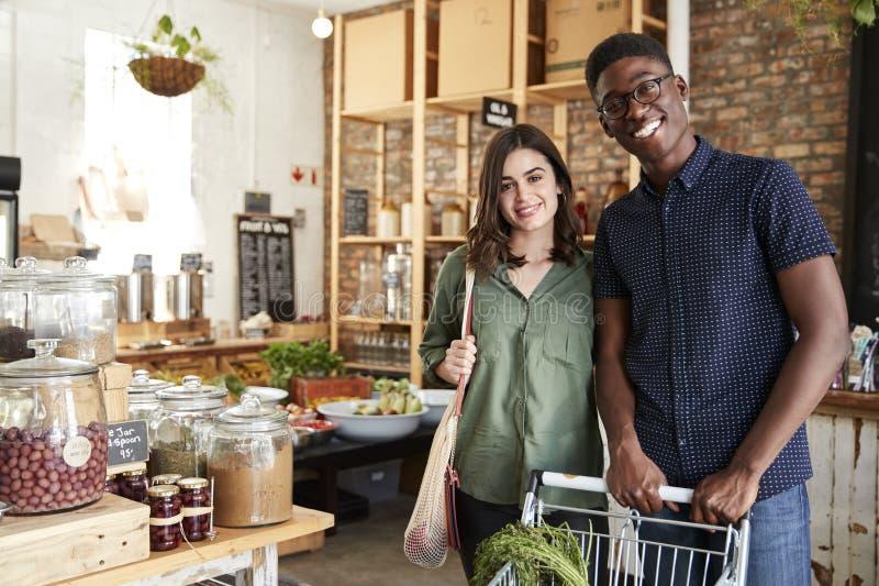 Stående av par med spårvagnen som köper nya frukt och grönsaker i plast- fri livsmedelsbutik arkivbilder