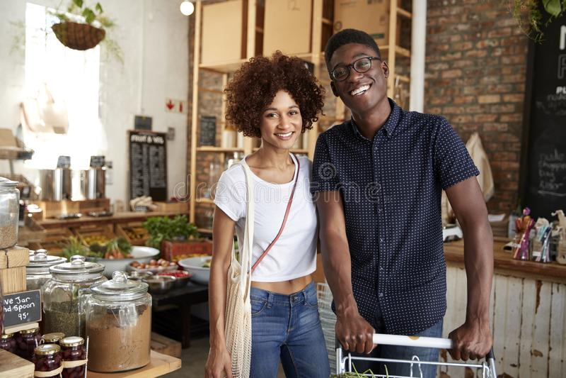 Stående av par med spårvagnen som köper nya frukt och grönsaker i plast- fri livsmedelsbutik fotografering för bildbyråer
