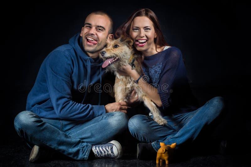 Stående av par och deras gulliga hund fotografering för bildbyråer