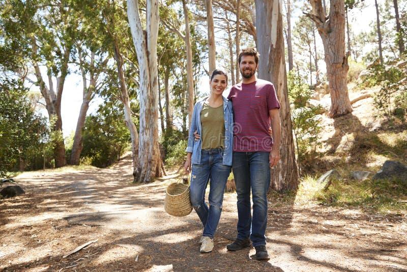Stående av par som fotvandrar längs Forest Path Together arkivfoto