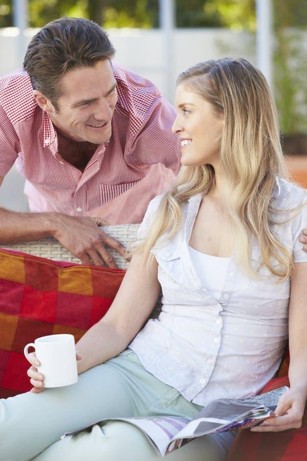Stående av par som kopplar av på utomhus- Seat royaltyfria foton