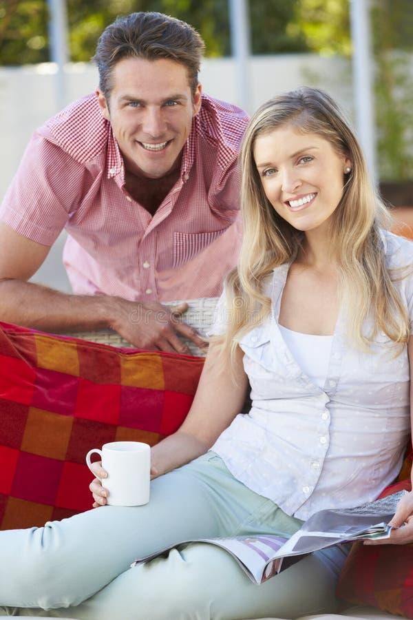 Stående av par som kopplar av på utomhus- Seat fotografering för bildbyråer