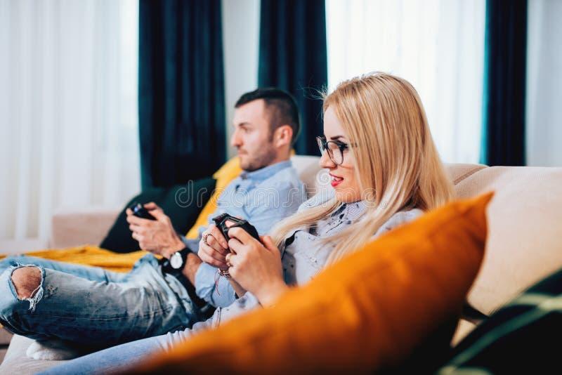 Stående av par som spelar videospel på den digitala konsolen Detaljer av den moderna livsstilen arkivfoto