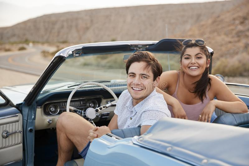 Stående av par som tycker om vägtur i öppen bästa klassisk bil royaltyfria foton