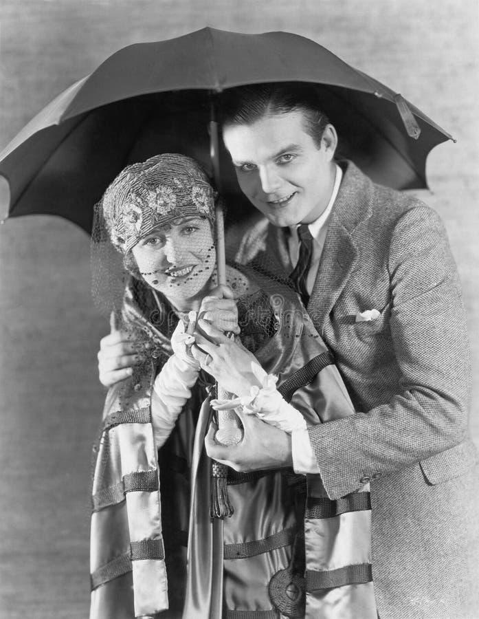 Stående av par under paraplyet (alla visade personer inte är längre uppehälle, och inget gods finns Leverantörgarantier som ther royaltyfri bild