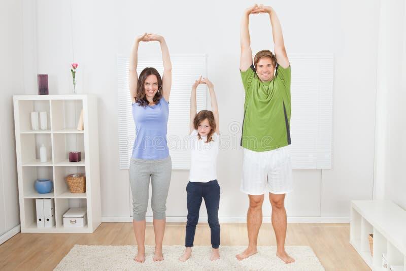 Stående av passformfamiljen som utför yoga royaltyfri bild