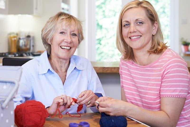 Stående av pensionären och mogna kvinnliga vänner som hemma sticker till royaltyfria foton