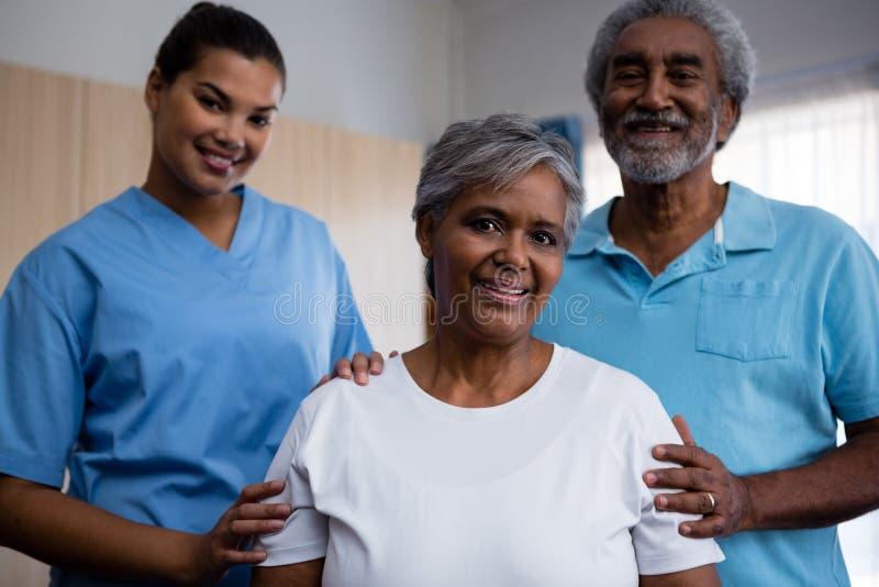 Stående av pensionärer med sjuksköterskan i avgånghem arkivbilder