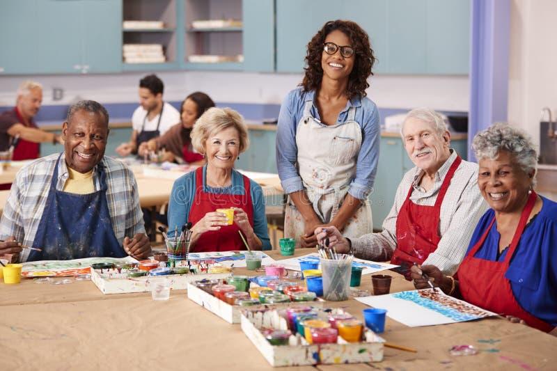 Stående av pensionerade pensionärer som deltar i Art Class In Community Centre med läraren royaltyfria foton
