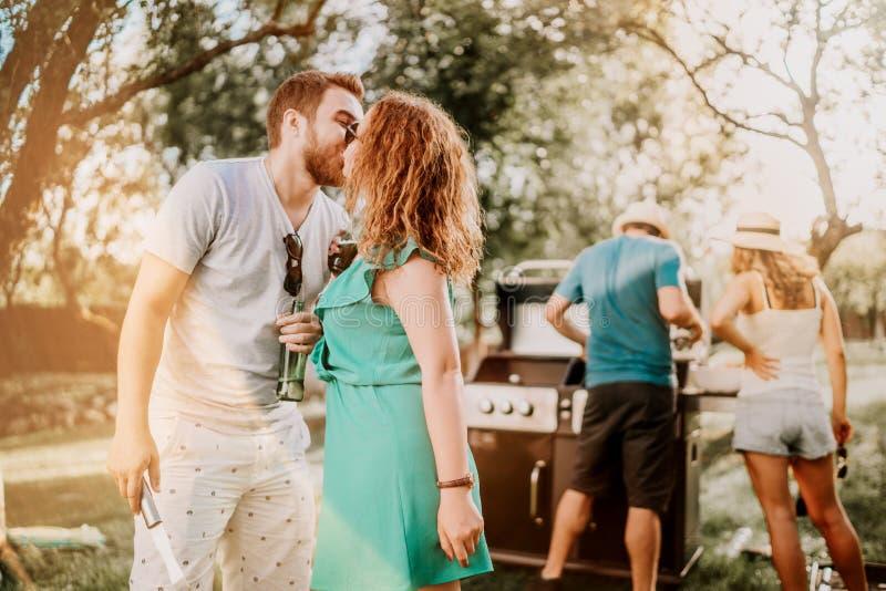 Stående av perfekta caucasian par som kysser på grillfestpartiet, vänner som har en bra tid royaltyfria bilder