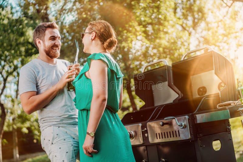 Stående av perfekta caucasian par som skrattar på grillfestpartiet, vänner som har en bra tid royaltyfria bilder