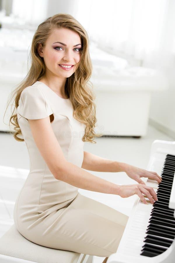 Stående av pianistsammanträde och spelapianot royaltyfri fotografi