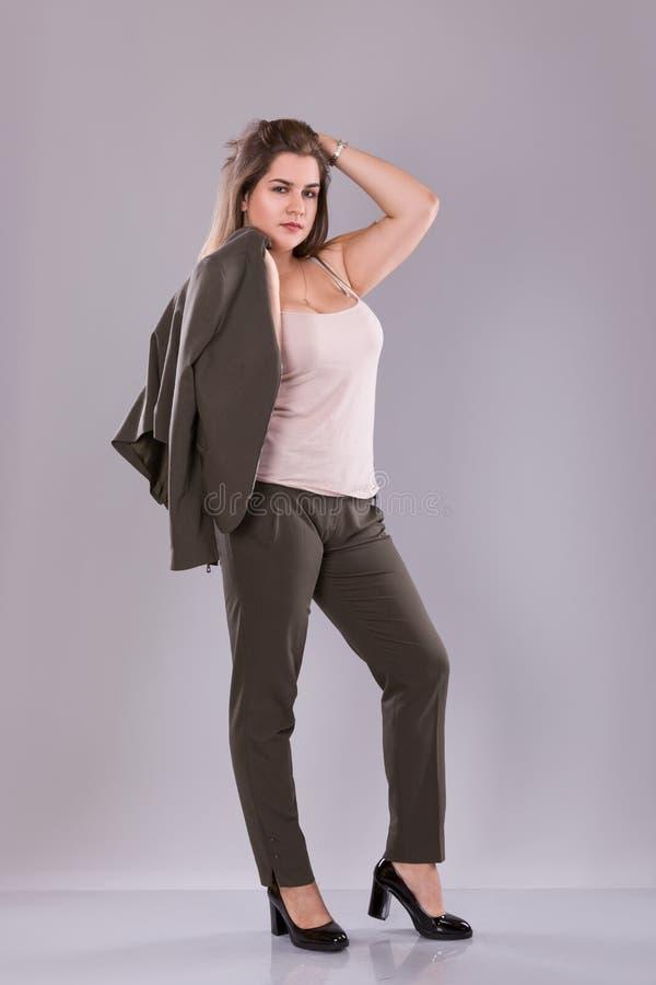 Stående av a plus den kvinnliga modellen för format som poserar i broundräkt över grå bakgrund royaltyfri foto