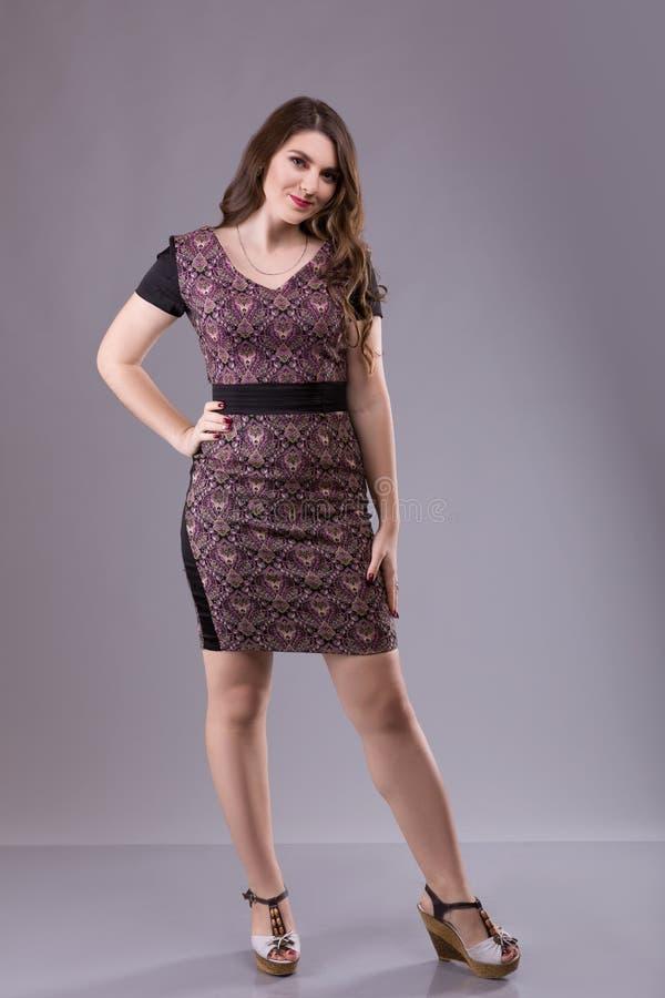Stående av a plus den kvinnliga modellen för format som poserar i broundräkt över grå bakgrund arkivfoto