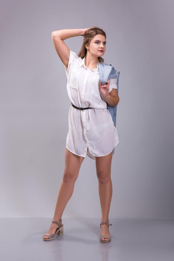 Stående av a plus den kvinnliga modellen för format som poserar i den vita klänningen över grå bakgrund arkivfoto